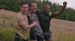 4K Portrait smiling mud race runners after slide down hill into cold muddy water Stock Footage