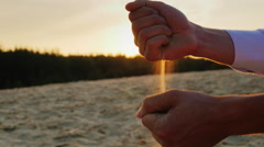 Hands of businessman man in a white shirt sifted sand through his fingers at Stock Footage