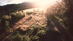 Aerial: Open Grassy Field in Late Sunset Light Over a Valley Stock Footage