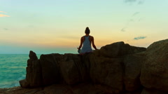 Young woman meditating on the rocks on the beach at sunrise background Stock Footage