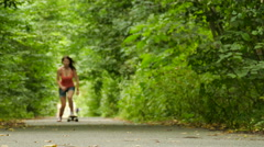 4K. Young beautiful girl figure  goes on  skateboard, Summer youth culture Stock Footage