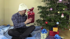Funny family man catch gift box and put under Christmas tree Stock Footage