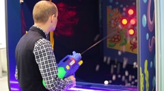 Man playing shooter video game in game center Stock Footage