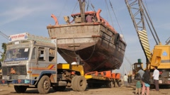 Crane lifting fishery boat on truck,Veraval,India Stock Footage