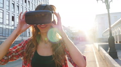 Girl with a device of virtual reality in the city Stock Footage