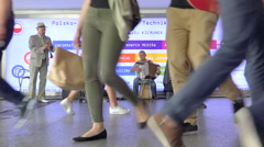 Crowd of people passing in front a jazz band in subway hallway - slow motion Stock Footage