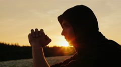 Dreamer at sunset. A young man sits in the hood profile to the camera. He is Stock Footage