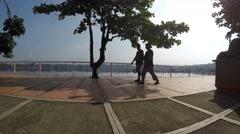 Two men walk lake shore gazebo. Silhouettes Stock Footage