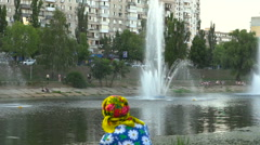 Old woman looking at the fountain in the park near the city river channel Stock Footage