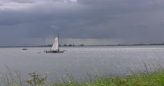 Traditional sailing boat lowering sail under dark cloud Stock Footage