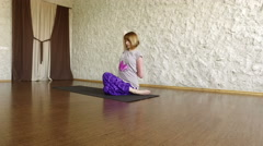 The young blonde girl practicing yoga in the hall. The pose of a cow's head. 4K Stock Footage