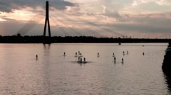 A group of people surfing with stand up paddle boards at beautiful sunset Stock Footage