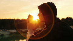 Young man praying at sunset. He sits in profile to the camera hood, clasped his Arkistovideo