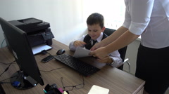 Boy depicts a businessman behind a Desk in the office, boy in office review Stock Footage