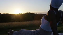 African american female sits back enjoying a sunset view, in slow motion Stock Footage