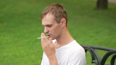 Man smoking thin cigarette at the park - stock footage