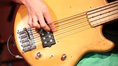 Young electric guitarist player playing bass guitar, closeup Stock Footage