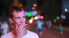 man smokes a cigarette on the street at night. night city - stock footage