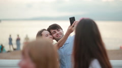 Beautiful couple taking selfie giving kiss on the beach on summer Stock Footage