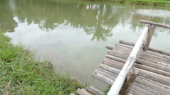 bamboo pier at the waterside of the pond - stock footage