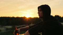 A young man in a hood finishes the last sip of beer from the bottle and throws Stock Footage