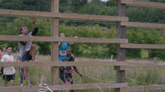 4K Competitors in endurance race, helping each other over climbing obstacle Stock Footage