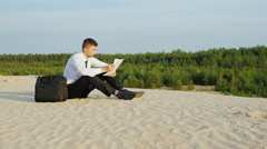Crane shot: Young businessman reading documents. He sits in a picturesque Stock Footage