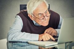 Elderly old man using laptop computer sitting at table - stock photo