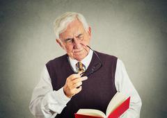 Elderly man holding book, glasses having eyesight problems Stock Photos