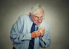 Greedy executive, CEO, boss mature man holding dollar banknotes Stock Photos