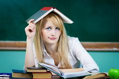 Annoyed, stressed, funny looking student with book on head, sitting at desk Stock Photos