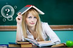 Student sitting at desk in classroom looking upwards, confused, thinking - stock photo