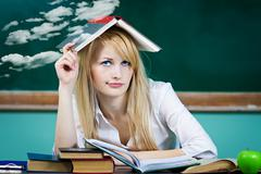 Student sitting at desk in classroom, looking upwards, confused, thinking Stock Photos