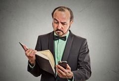 Skeptical man reading news on smartphone, holding book Stock Photos