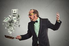 Middle age businessman juggling money dollar bills - stock photo