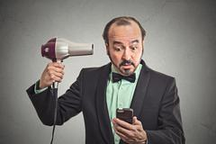 Business man reading news on smartphone holding hairdryer Stock Photos