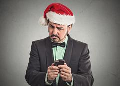 skeptical man wearing santa claus hat looking at smartphone - stock photo