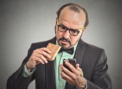 Man reading message on smart phone eating cookie Stock Photos