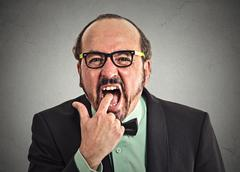 Disgusted man with finger in mouth Stock Photos