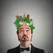 Middle aged man looking up city plan above head Stock Photos