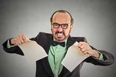 Angry businessman tearing a document to pieces Stock Photos