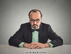 Sad stressed man sitting at office desk Stock Photos