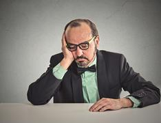 Desperate businessman sitting leaning on a desk looking down Stock Photos