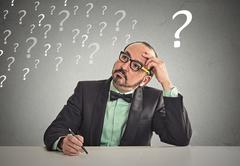 puzzled business man sitting at table scratching his head thinking - stock photo