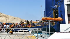 Tourists arriving on  a super ferry at Santorini's port Stock Footage