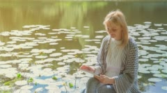 Beautiful girl using Tablet PC sitting near lake in city park 2 on sunset Stock Footage