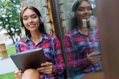 Joyful young woman entertaining with gadget Stock Photos
