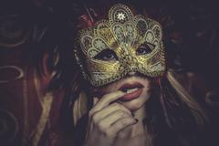Blonde with gold mask on red cloth embroidered golden thread, mystery and sen Stock Photos