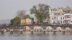 Bridge with people walking on lake Pichola,Udaipur,India Stock Footage