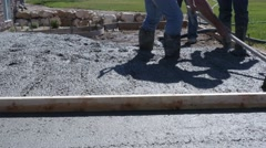 Workers levelling freshly poured concrete patio outside Stock Footage